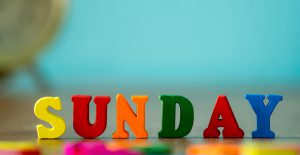 Colorful wooden word sunday on wooden table and vintage alarm clock
