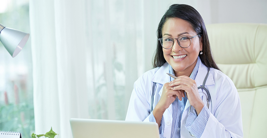 Smiling ethnic doctor sitting at desk in office